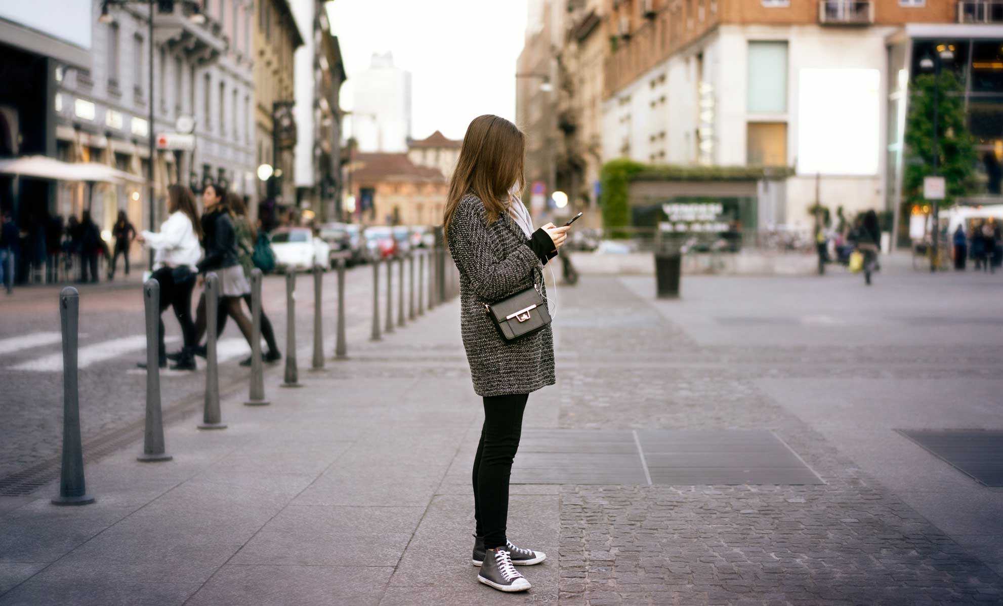 Girl standing on the street with an iphone